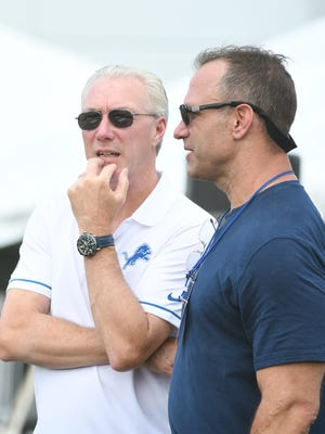 Lions president Rod Wood and former Detroit Lions linebacker Chris Spielman chat on the side of the field during practice.