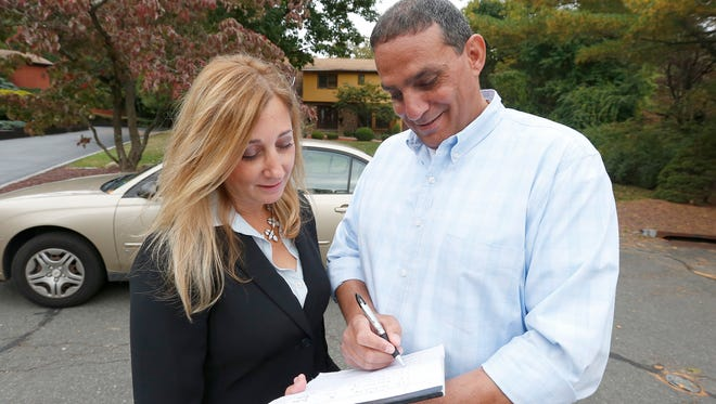 Leslie Kahn, Clarkstown Deputy Town Attorney, left, and Code Enforcement Officer Raymond Francis look over a list of previous violation in front of a residence in New City on Thursday, October 13, 2016.