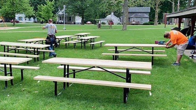 Volunteers help put the finishing touches on picnic tables that were built to replace those that were loaned out earlier this month.
