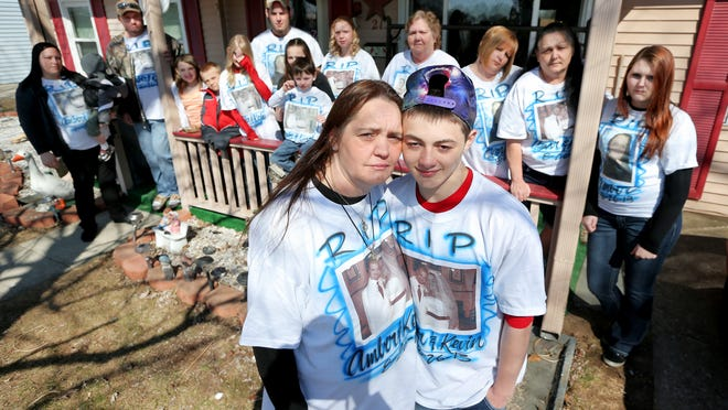 Isiah Stitt, 15, is embraced by his great aunt, Denise Owens, outside his great-grandmother's home in Edinburgh as other family members gather. The T-shirts show Isiah's mother and father, who were both killed in the father's murder-suicide.
