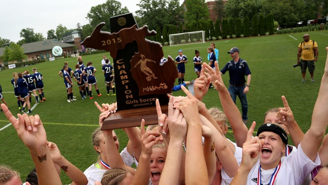 Hudsonville Unity Christian celebrate with the Division 3 girls soccer state title trophy after beating Birmingham Detroit County Day in double overtime Friday at Michigan State.