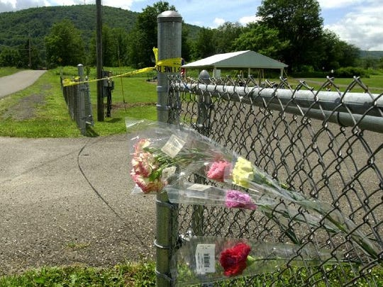 Flowers added to the fence at the entrance to the park on Grange Hall Rd. in Kirkwood, two days after Kevin Tarsia was killed in 2002.