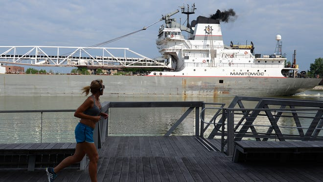 A morning jogger trots along CityDeck in Green Bay as the freighter Manitowoc eases through the Walnut Street Bridge on the Fox River.