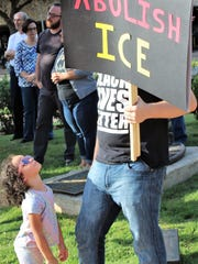 About 200 people of all ages attended the Families Belong Together rally Saturday at Everman  Park, including this man carrying a sign to abolish Homeland Security's Immigration and Customs Enforcement branch.