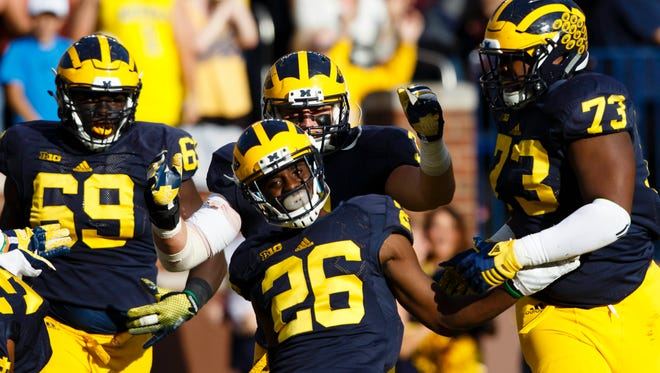 Michigan Wolverines cornerback Jourdan Lewis (26) celebrates with teammates after he scores a touchdown on an interception in the second quarter against the Northwestern Wildcats at Michigan Stadium.