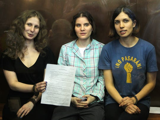Feminist punk group Pussy Riot members Maria Alekhina (from left), Yekaterina Samutsevich and Nadezhda Tolokonnikova show the court's verdict as they sit in a glass cage at a courtroom in Moscow on Aug 17, 2012. A judge found them guilty of hooliganism, in a case that drew widespread international condemnation as an emblem of Russia's intolerance of dissent.
