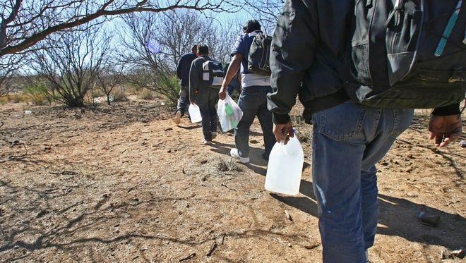 Varios inmigrantes cruzan por el desierto de Arizona.