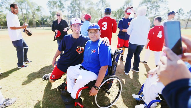 Minnesota Twins' Tyler Benninghoff spends time with Angel De Dios, 17, during a youth baseball clinic recently at Three Oaks Park in Fort Myers..