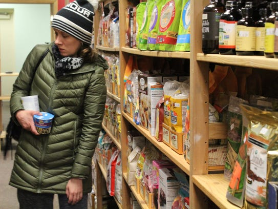 A customer looks at the walls of food in Downtown Grocery's