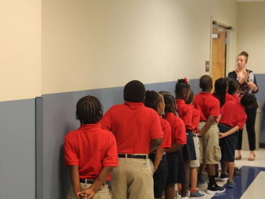 Students line up at their teacher's instruction while