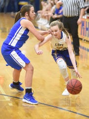 Mountain Home's Kaylee Crownover dribbles past a Harrison defender on Monday night.