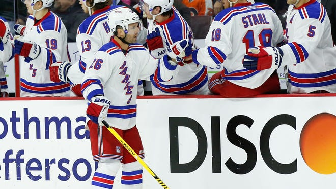 Rangers right wing Martin St. Louis is congratulated by teammates after scoring a goal for his 1,000th career NHL point during the second period of the Rangers' 3-0 win over the Flyers on Friday at Wells Fargo Center.