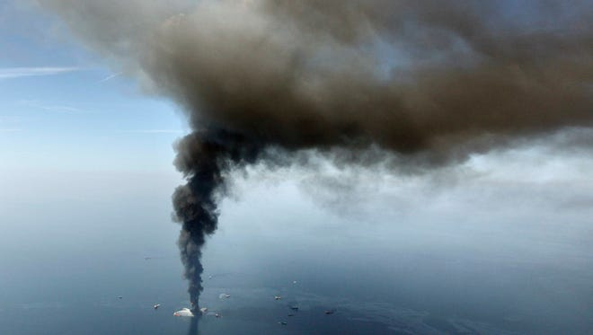In this April 21, 2010, file photo by Gerald Herbert, the Deepwater Horizon oil rig burns in the Gulf of Mexico.