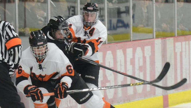 Northville's Jack Sargent (left) and Brendan Hicks (right) team up to put the squeeze on a Novi player during Tuesday's game at Novi Ice Arena.