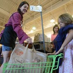 Whole Foods Market cashier Ona Fisher, left, puts a bag of groceries into Elliana Beno's kids cart at the Fort Collins Whole Foods on July 1.