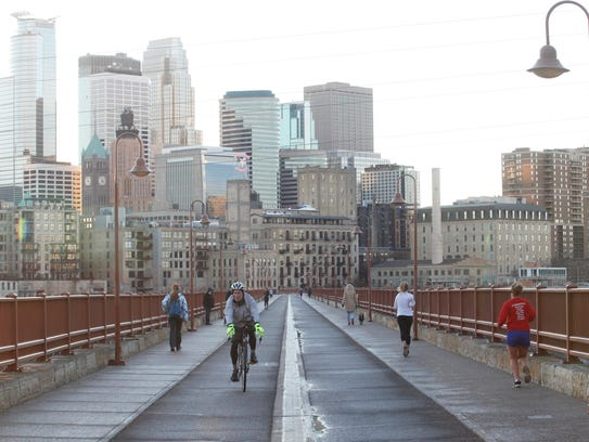 A cyclist and runners cross the Stone Arch Bridge on