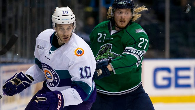 Everblades' Matt Berry (27) eyes the puck as he jousts with Solar Bears' Jon Jutzi (10) during the first period of Game 2 of the Kelly Cup Playoffs, South Division semifinals at Germain Arena Friday, April 14, 2017 in Estero, Fla.