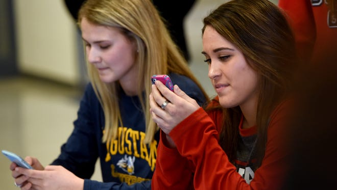O'Gorman's Theresa Pujado and Isabelle Hedge look at their phones after a signing ceremony on Wed., Feb. 1, 2017. Pujado intends on playing soccer at University of Nebraska - Lincoln and Hedge will play at Augustana University.