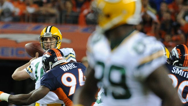 Green Bay Packers quarterback Aaron Rodgers (12) throws downfield for wide receiver James Jones (89) as he is hit by Denver Broncos outside linebacker DeMarcus Ware (94) against the Denver Broncos at Sports Authority Field on Nov. 1, 2015.