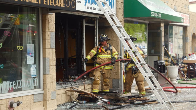 Firefighters and investigators at the scene of a Friday morning fire on East Main Street in Denville. The fire looks to have begun at the restaurant, Yama Sushi. May 18, 2018. Denville, NJ