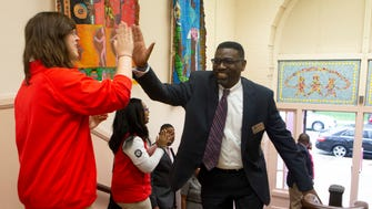 Milwaukee Public Schools Interim Superintendent Keith  Posley gives a high-five as he enters Clarke Street School Monday morning.