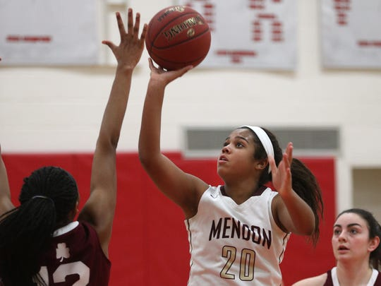 Mendon's Lexi Green (20) shoots over Aquinas'  Nia Williams-Matthews during a game last season. Green averaged 15 points per game as a freshman in 2017-18.