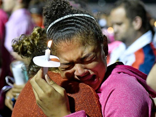 Classmates of Trinity Gay gathered in her memory at Lafayette High School, Monday, Oct. 17, 2016, in Lexington, Ky. Several thousand people, including Tyson Gay, turned out Monday night for a candlelight vigil in Kentucky to honor Gay's 15-year-old daughter, Trinity, who was fatally shot over the weekend. (AP Photo/Timothy D. Easley)