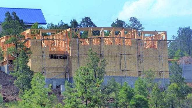 A large home is being built on lower Moon mountain with an interrupted view of Sierra Blanca Peak.