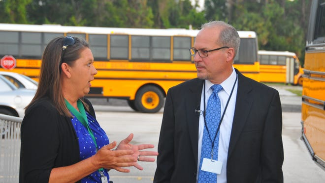 Before boarding a bus, Misty Belford chats with Dr, Mark Mullins. South Lake Elementary School in Titusville was closed by the school board in 2013. It was reopened Friday as a school of choice and was the first school visited by incoming superintendent Mark Mullins who road the school bus to the school.