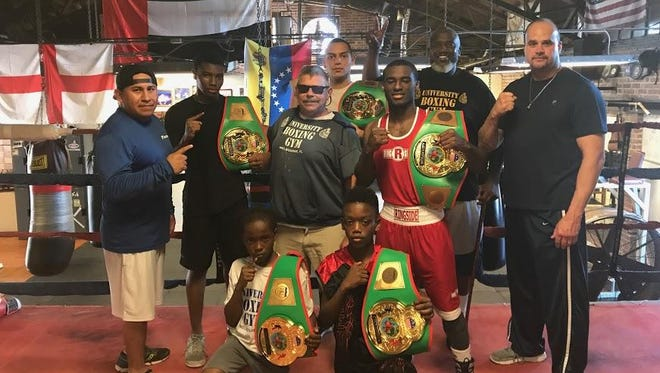 """University Boxing Club's Kevion Williams, 9, Alex Bray, 10, Omari Peebles, 15, Jahavanta Johnson, 24, and Angelo """"Rocky"""" Calderone, 22, were all victorious in Jacksonville last weekend. In sunglasses is University Boxing Club owner Gary Gregory."""