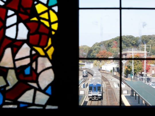 A train is seen arriving through a window next to a