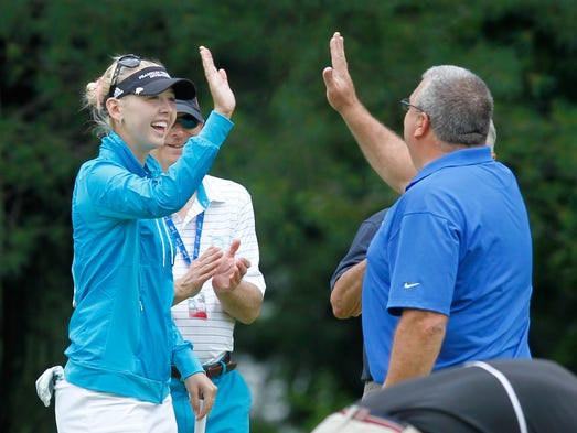 George Smith, right, gets a high-five from his playing partner LPGA pro Jessica Korda after he sank his birdie putt on the 5th hole during the Wegmans LPGA Championship Pro Am held Wednesday, Aug, 13, 2014 at Monroe Golf Club.