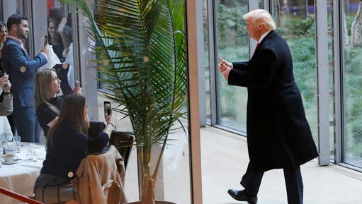President-elect Donald Trump gestures to people seated in a restaurant as he leaves the New York Times building following a meeting, Tuesday, Nov. 22, 2016, in New York.