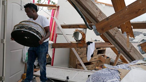Dwight Powell recovers mirrors from the bathroom of his master bedroom a day after a tornado touched down in eastern New Orleans, Wednesday, Feb. 8, 2017.