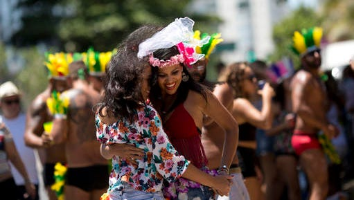 """In this Feb. 19, 2017 photo, a couple dances during the """"If you don't give me....then you lend me"""" Carnival street party on Ipanema beach, in Rio de Janeiro, Brazil. The typical view of Carnival in Brazil is anything goes, with no headdress too big, no outfit too small, no song too ribald, but this year some organizers of the world's best known party are drawing the line at lyrics that are sexist, homophobic or racist."""