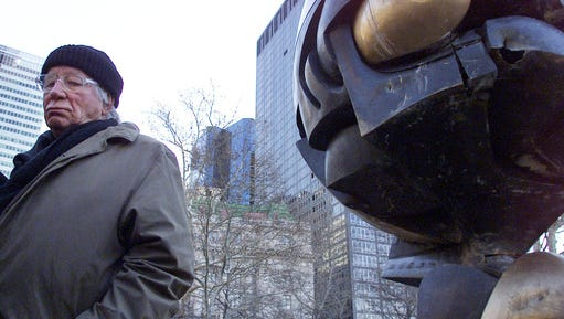 "FILE - In this file photo dated Monday, March 11, 2002, German artist Fritz Koenig stands next to his bronze sculpture ""The Sphere"" after a dedication ceremony in New York.  Koenig who's artwork ""The Sphere"" became a symbol of resilience after the 9/11 attacks in New York, died Wednesday Feb. 22, 2017 aged 92, according to news reports and Bavaria state's Ministry of Culture."