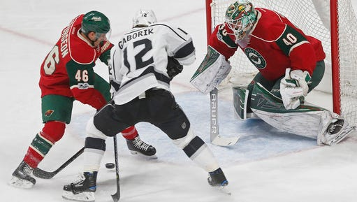 Minnesota Wild's Jared Spurgeon (left) tries to keep Los Angeles Kings' Marian Gaborik of Czech Republic away from the puck as goalie Devan Dubnyk guards the net in an NHL hockey game, Monday, Feb. 27, 2017, in St. Paul.