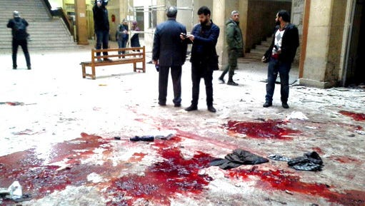 In this photo released by the Syrian official news agency SANA, journalists gather next of blood inside the main judicial building which attacked by a suicide bomber, in Damascus, Syria, Wednesday, March 15, 2017.