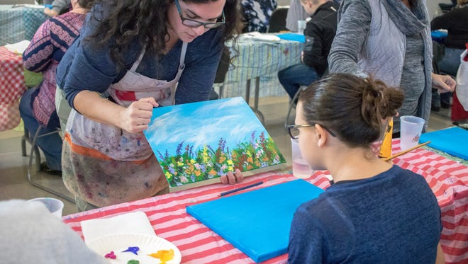 Local artist Mackenzie Warren, of Oak Tree Art Studio, helps out student Macy Merrill during the 'Side by Side Art' class on Saturday in honor of Developmental Disabilities Awareness Month.