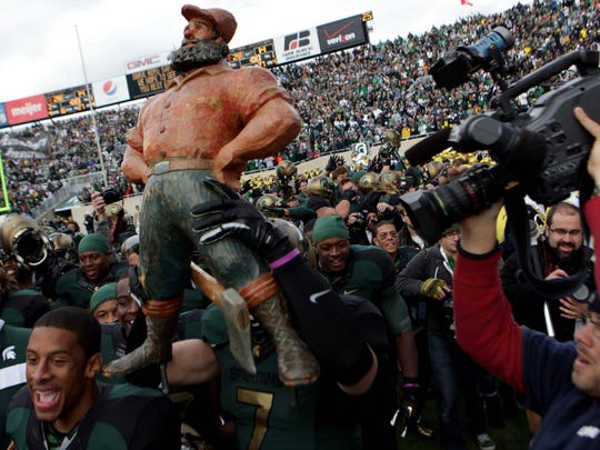 Michigan State players hold up the Paul Bunyan Trophy