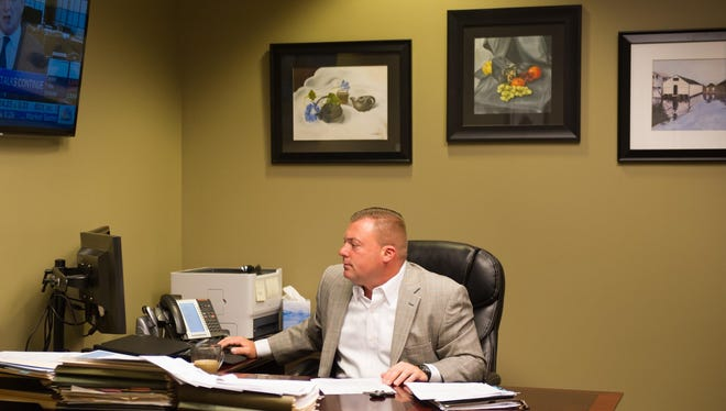 Senior Vice President of APFS Wealth Management Inc., Jeremy Raco of Penfield, prepares for a client meeting at the company's offices in Linden Oaks.