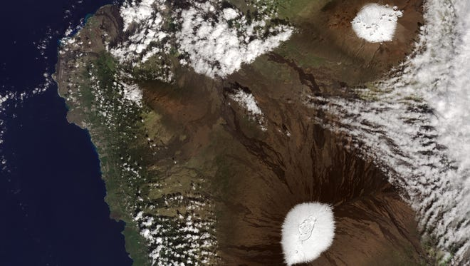 Almost every year, snow falls on the peaks of Mauna Kea and Mauna Loa volcanoes. This photo taken by a NASA satellite on Dec. 25, 2016.