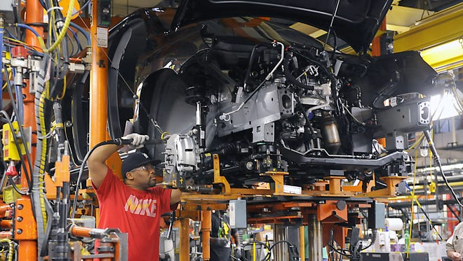 Ernest Card helps build vehicles at General Motors Co.'s Lansing Delta Township assembly plant. The plan;ts holiday shut down will last three weeks for construction work at its expansion facility.