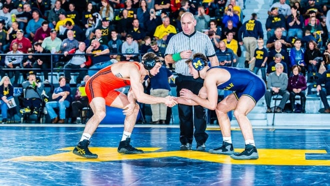 Hartland native Reece Hughes (right) made his debut in the University of Michigan's starting lineup on Saturday, beating Oregon State's Billy Bigelow (left), 5-0.