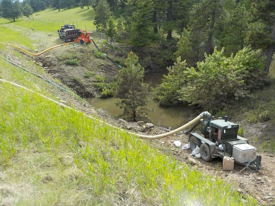 A temporary culvert is pumping water from the north