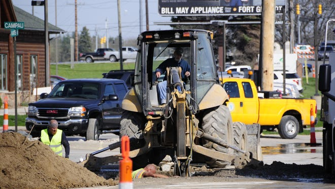 Port Huron Township workers look for a water main break on Water Street.