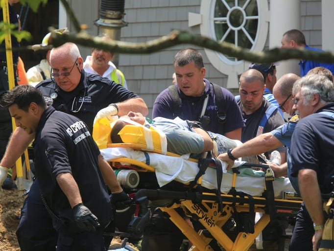 Police officers and firefighters rescue a construction worker after being trapped in a trench for over an hour outside the home  at 15 Bradford Avenue in Rye on July 31, 2014