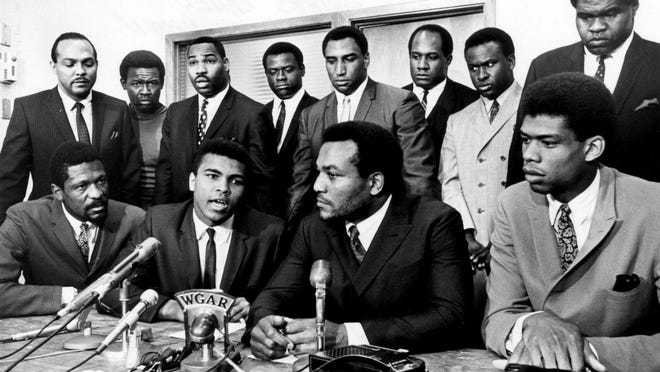 Front row, from left, Bill Russell, Muhammad Ali, Jim Brown and Kareem Abdul-Jabbar discuss their meeting with Ali in a show of athlete solidarity.