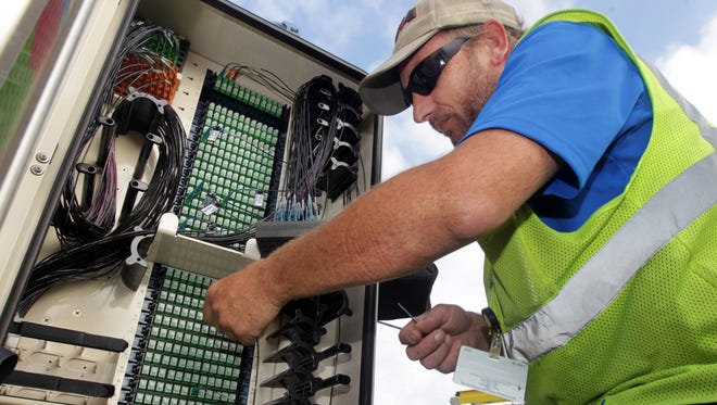 Nick Hoyes, of Cincinnati Bell, connects fiber optic service to a home in Morgan Township at a fiber optic distribution hub on Jenkins Road.