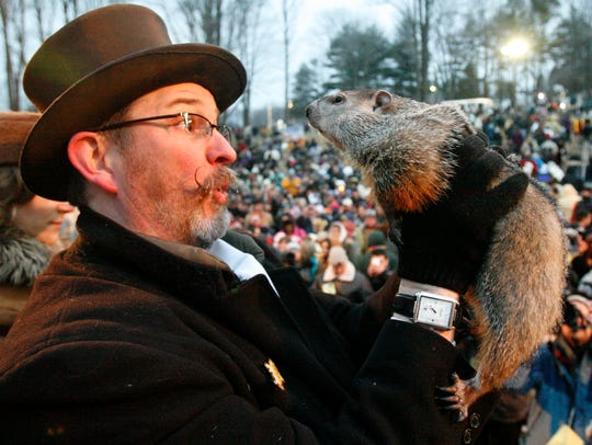 Punxsutawney Phil, right, is held by Ben Hughes after
